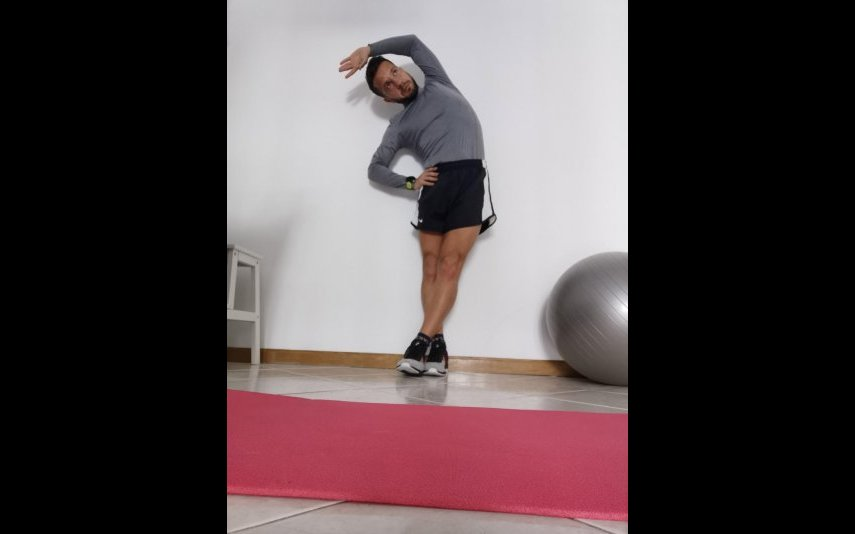 Com as costas em contato com a parede, simule uma posição sentada colocando a coxa em rotação externa, pressionando o joelho em direcção ao chão e traccionando o tornozelo em direcção ao tecto. Objetivo:  alongar os músculos glúteos (foto bilateral)